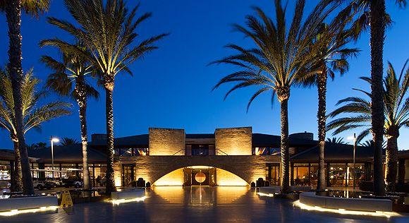 Al anochecer el hotel CLUB POLLENTIA RESORT, parece un decorado, un primer plano con un muro, con grandes ventanas en los laterales y un gran arco en el centro