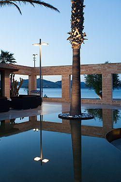 Entre los pilares de luz que sujetan los ventanales, podemos contemplar una zona de estar, un oasis, unos lagos, que a su vez rodean unas curiosas palmeras, que asoman su cuello iluminado por encima del muro